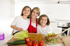 Young mother in cook apron and sweet beautiful twin daughters cooking preparing together salad Royalty Free Stock Image