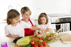 Young mother in cook apron and sweet beautiful twin daughters cooking preparing together salad Royalty Free Stock Photography