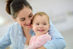 Young mother cuddling her smiling baby Royalty Free Stock Photography