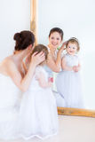 Young mother and curly daughter in front of mirror Stock Photography