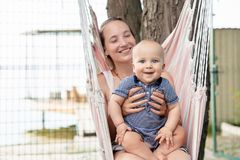 Young mother with cute baby boy sitting and relaxing on hammock near river or lake. Mom and kid having fun at summer outdoors. Hap stock images