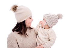Young mother and cute baby daughter in winter clothes looking at each other isolated on white. Background stock images