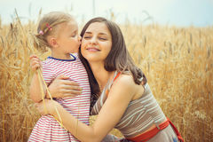 Young mother with cute daughter at grain field Royalty Free Stock Photos