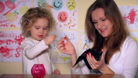 Young mother and cute daughter putting coins into piggy bank. Static shot. 4K UHD stock video footage