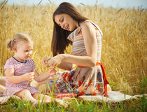 Young mother with cute daughter at wheat field Royalty Free Stock Photo
