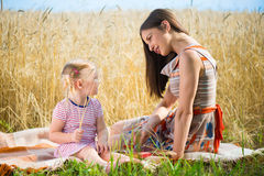 Young mother with cute daughter at wheat field Royalty Free Stock Photos