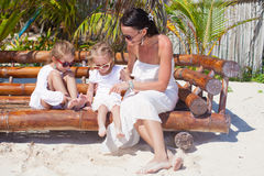 Young mother with cute daughters sitting in beach Stock Photo