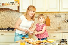 Young mother and cute little daughter bake cookies and having fun in the kitchen. Young mother and cute little daughter bake cookies and having fun in a kitchen Royalty Free Stock Images