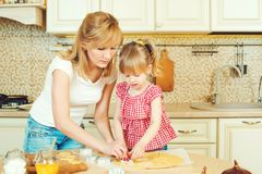 Young mother and cute little daughter bake cookies and having fun in the kitchen. Young mother and cute little daughter bake cookies and having fun in a kitchen Royalty Free Stock Photography