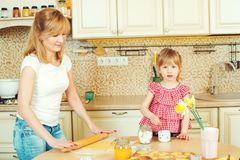Young mother and cute little daughter bake cookies and having fun in the kitchen. Young mother and cute little daughter bake cookies and having fun in a kitchen Royalty Free Stock Photos