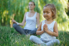 Young mother and cute little daughter meditating in lotus pose together. At green summer park Royalty Free Stock Photos