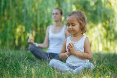 Young mother and cute little daughter meditating in lotus pose together. At green summer park Stock Image