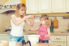 Young mother and cute little daughter preparing the dough, bake cookies and having fun in a kitchen. Young mother and cute little daughter preparing the dough stock photography