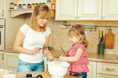 Young mother and cute little daughter preparing the dough, bake cookies and having fun in a kitchen. Young mother and cute little daughter preparing the dough royalty free stock image