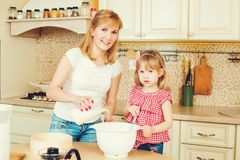 Young mother and cute little daughter preparing the dough, bake cookies and having fun in the kitchen. Happy family are preparing bakery together stock image