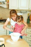 Young mother and cute little daughter preparing the dough, bake cookies and having fun in the kitchen. Happy family are preparing bakery together royalty free stock photo