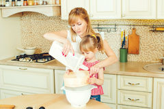 Young mother and cute little daughter preparing the dough, bake cookies and having fun in the kitchen. Happy family are preparing bakery together royalty free stock image