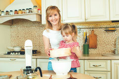 Young mother and cute little daughter preparing the dough, bake cookies and having fun in the kitchen. Happy family are preparing bakery together stock photography