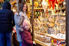 Young mother and cute little daughter selecting decoration on Christmas market. Beautiful woman and adorable kid girl. Young mother and cute little daughter royalty free stock photos