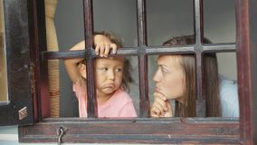 Mother and little daughter are looking out the window with boring emotions. Stock Photography