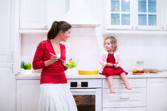 Young mother and daughter baking a pie together Royalty Free Stock Photo