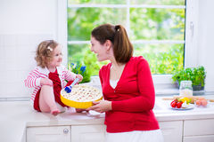Young mother and daughter baking a pie together Stock Images
