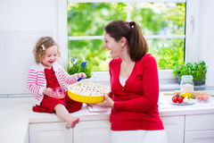 Young mother and daughter baking a pie together Royalty Free Stock Image