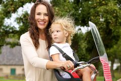 Young mother and daughter on bicycle ride in the park Royalty Free Stock Images