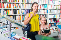 Young mother with daughter in book shop. Portrait of smiling young mother with daughter picking textbooks for school in book shop Royalty Free Stock Photos