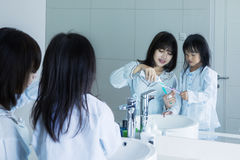 Young mother and daughter brush teeth Stock Photos