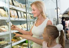 Mother with daughter buying chilled foods in supermarket. Young mother with daughter buying chilled foods in supermarket royalty free stock photography