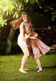 Young mother and daughter dancing on grass at yard Stock Image