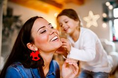 Young mother with daughter decorating Christmas tree together. Stock Photo