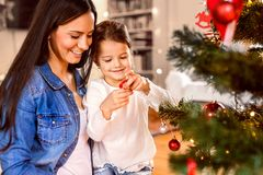 Young mother with daughter decorating Christmas tree together. Young mother with his little daughter at home decorating Christmas tree together Stock Photo