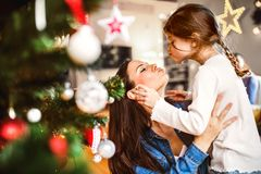 Young mother with daughter decorating Christmas tree together. Young mother with his little daughter at home decorating Christmas tree together Stock Images
