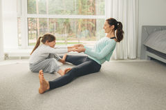 Young mother and daughter doing morning yoga exercise. Mother and daughter making gymnastics and stretching at home. Family healthy lifestyle concept Stock Photos
