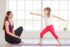 Young mother and daughter doing yoga exercise Royalty Free Stock Images