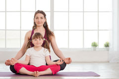 Young mother and daughter doing yoga exercise Royalty Free Stock Photos