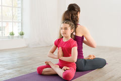 Young mother and daughter doing yoga exercise Royalty Free Stock Image