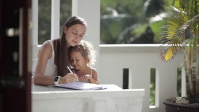 Young mother with daughter drawing at balcony with palm trees on the background. Young mother with cute little daughter drawing at balcony with palm trees on the stock video footage