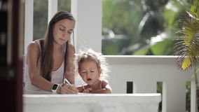 Young mother with daughter drawing at balcony with palm trees on the background. Young mother with cute little daughter drawing at balcony with palm trees on the stock footage