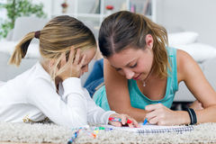 Young mother and daughter drawing on the notebook at home. Royalty Free Stock Photo