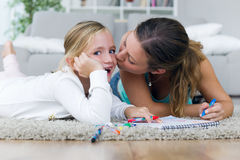 Young mother and daughter drawing on the notebook at home. Stock Photo