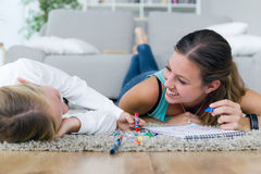 Young mother and daughter drawing on the notebook at home. Royalty Free Stock Photos