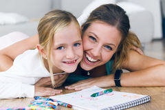 Young mother and daughter drawing on the notebook at home. Stock Image