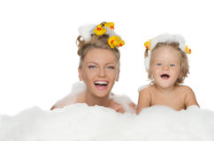 Young mother, daughter with ducks and soap foam. Isolated on white stock photography