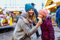 Young mother and daughter eating white chocolate covered fruits on skewer on traditional German Christmas market. Happy girl and women on traditional family stock photo