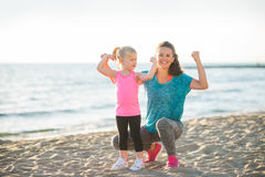 Young mother and daughter in fitness gear on beach flexing arms Stock Photo