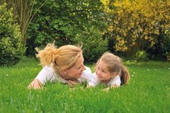 Young mother and daughter on the grass Stock Photos