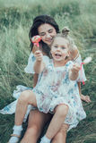 The young mother and daughter on green grass Stock Image